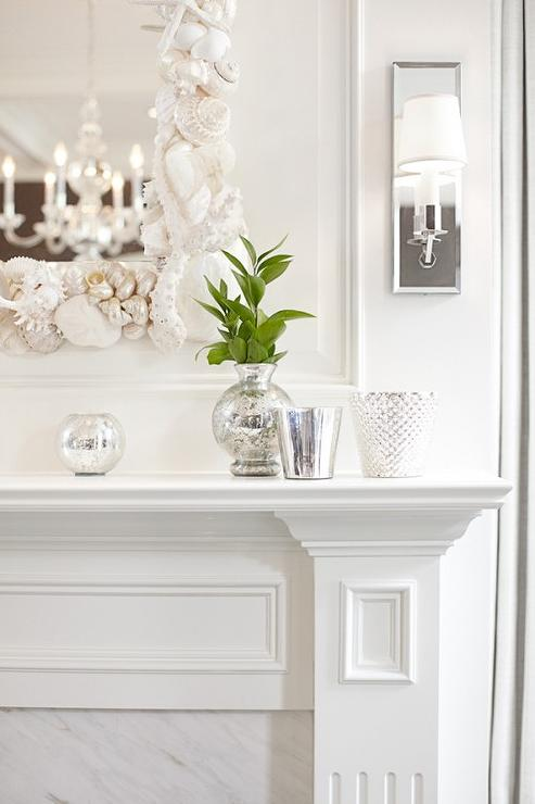 White Fireplace With White Seashells Mirror And Mirrored Sconces