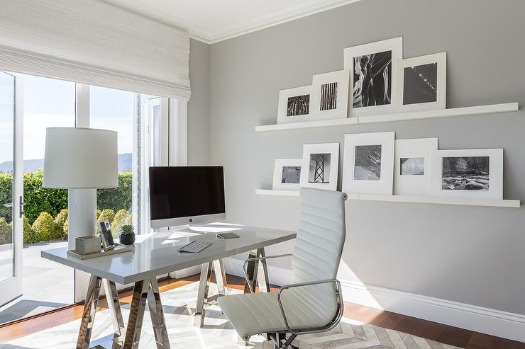 chic sleek office features a chrome sawhorse desk and an eames management chair placed atop a white and gray herringbone rug placed in front of stacked chic home office features