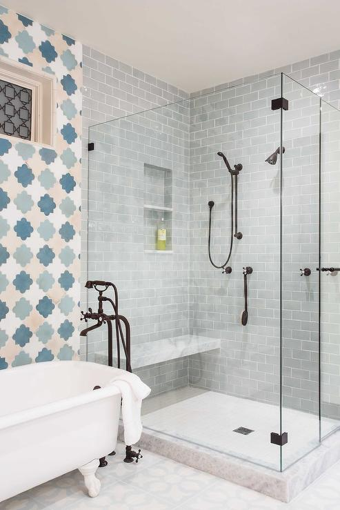 blue and gray bathroom boasts a claw foot tub and a bronze vintage tub filler lining a wall clad in blue quatrefoil tiles - Vintage Tub