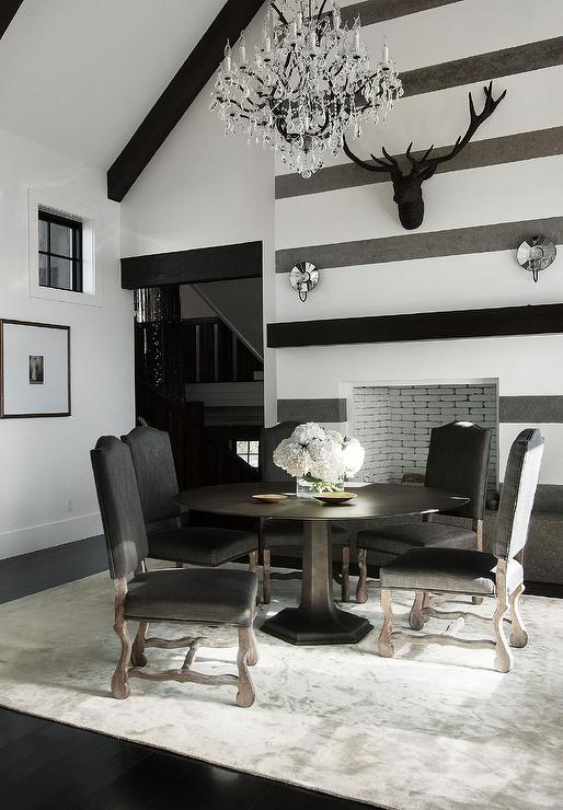 Contemporary Cabin Dining Room Boasts A White Vaulted Ceiling Dotted With Dark Wood Beams And Crystal Chandelier Illuminating Round Black Table