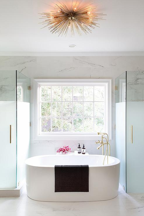 Oval Freestanding Tub Flanked by a Frosted Glass Shower and