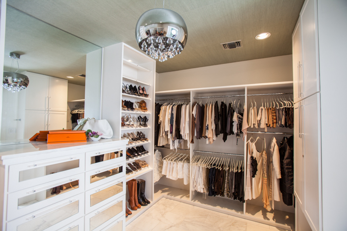White Walk In Closet With Hermes Orange Accents And Mirrored Dresser