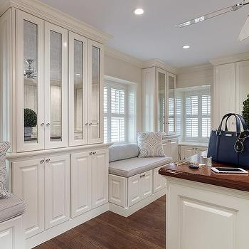 Walk In Closet With Antiqued Mirrored Cabinets And Glossy Wood Island Countertop