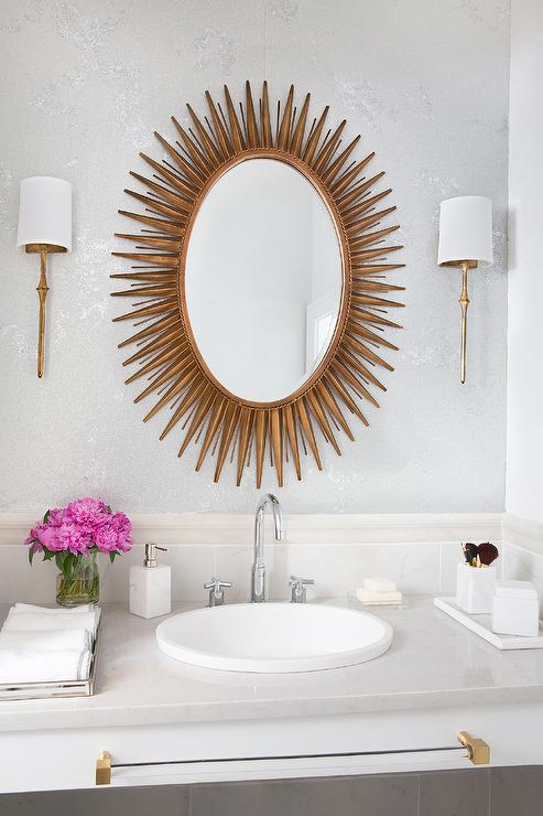 Well Designed Bathroom Features Walls Covered In White And Silver Wallpaper  Accented By Two Antique Brass Dauphine Sconces And A Stunning A Surya Gold  Oval ...