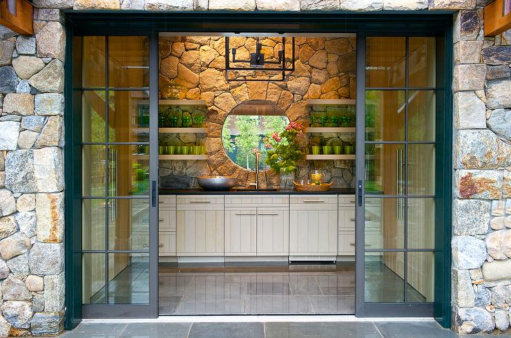 Stone pool house with fireplace and teak chairs for Sliding glass doors garden