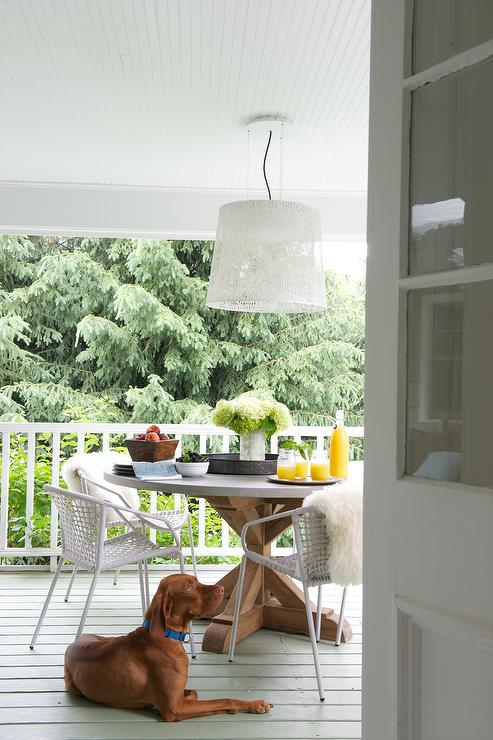 Covered Deck With Round Wood And Gray Marble Dining Table And White Woven  Chairs