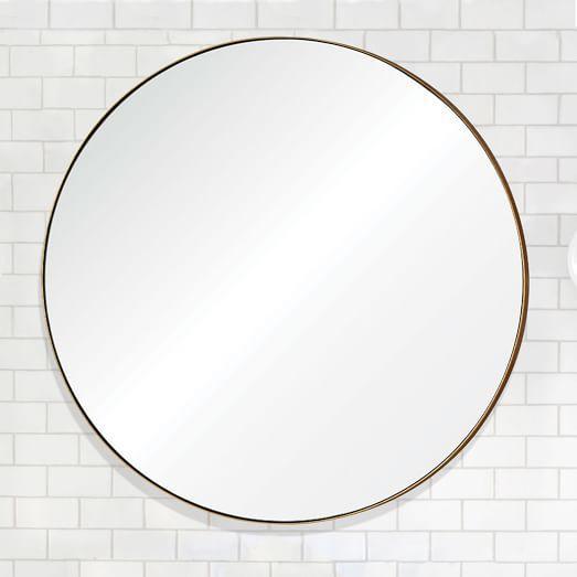 thin gold framed round wall mirror