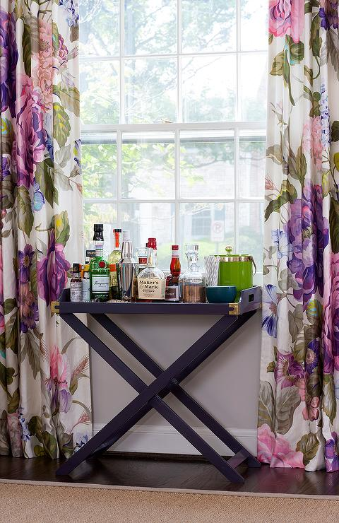 Purple Dining Room Features A Campaign Bar Table Adorned With Brass Accents Placed Under Window Dressed In Floral Curtains