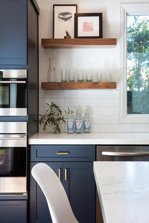 Fantastic Kitchen Features Navy Blue Shaker Cabinets Adorned Aged Brass Pulls Paired With White Quartz Countertops That Resemble Marble And A Stacked