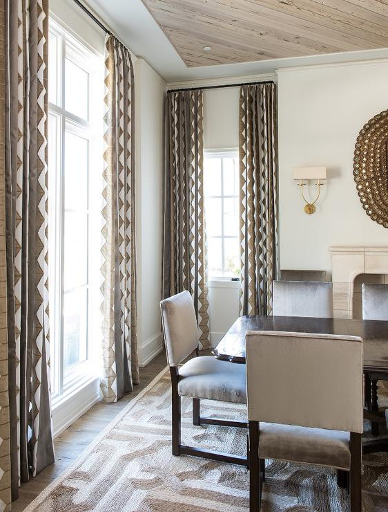 Brown And Gray Dining Room Features A Dark Stained Table Lined With Velvet Chairs Placed Atop Trellis Rug