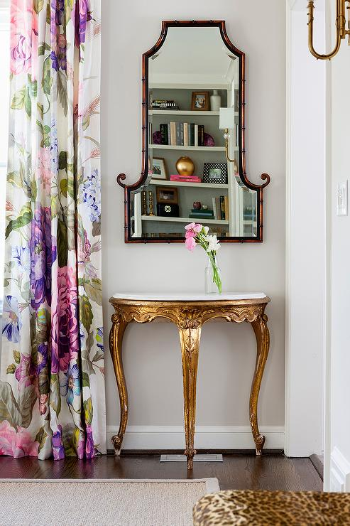 Chic Dining Room Boasts A Marble And Gold Leaf Half Moon Table Bamboo Mirror Placed Next To Window Dressed In Purple Floral Curtains