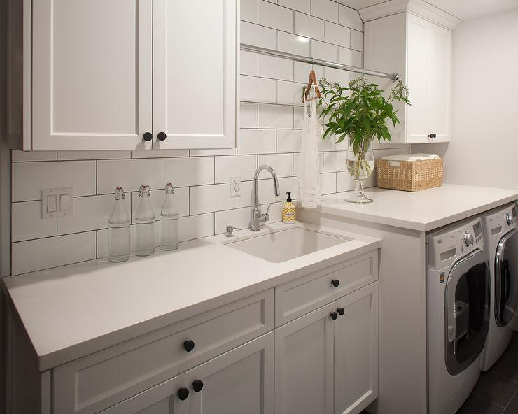 Black And White Laundry Room With Herringbone Tile Floor