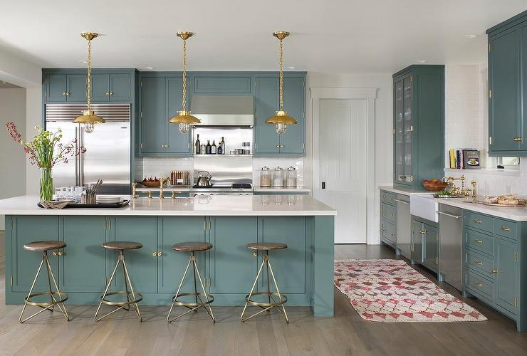 Green Kitchen Cabinets With Brass Hardware And Lights