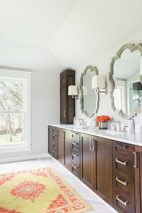 fabulous bathroom features a wall of walnut stained vanity cabinets