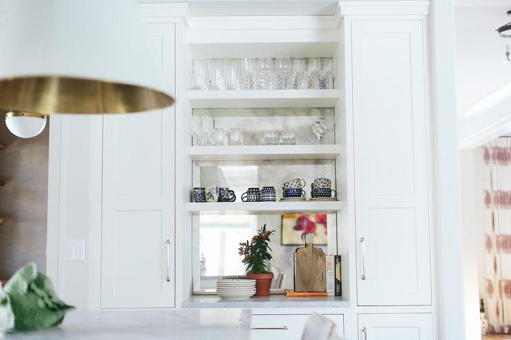 Chic Kitchen Features Stacked Built In Shelves Accented With An Antiqued Mirrored Backsplash Flanked By Cabinets