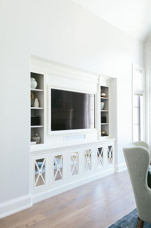 Chic Living Room Nook Is Filled With A Flat Panel Tv Niche Flanked By Shelving As Well Mirrored X Front Cabinets