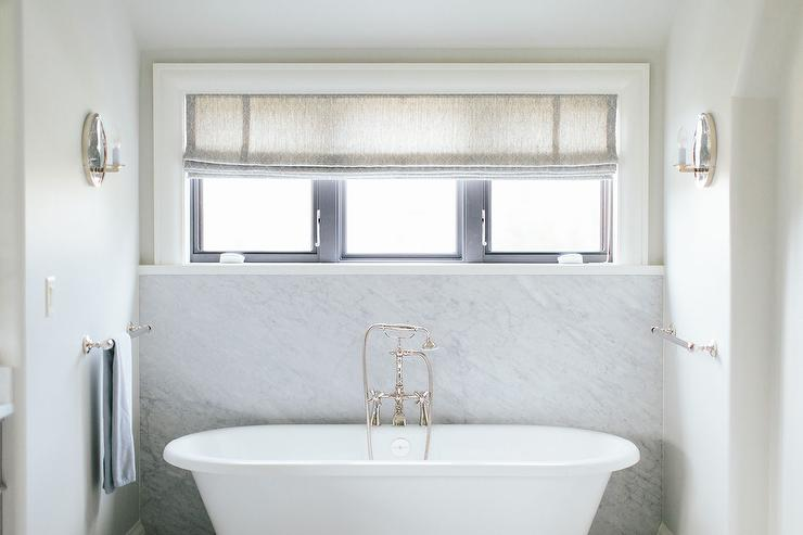 Roll Top Bathtub With Marble Slab Backsplash Under Windows