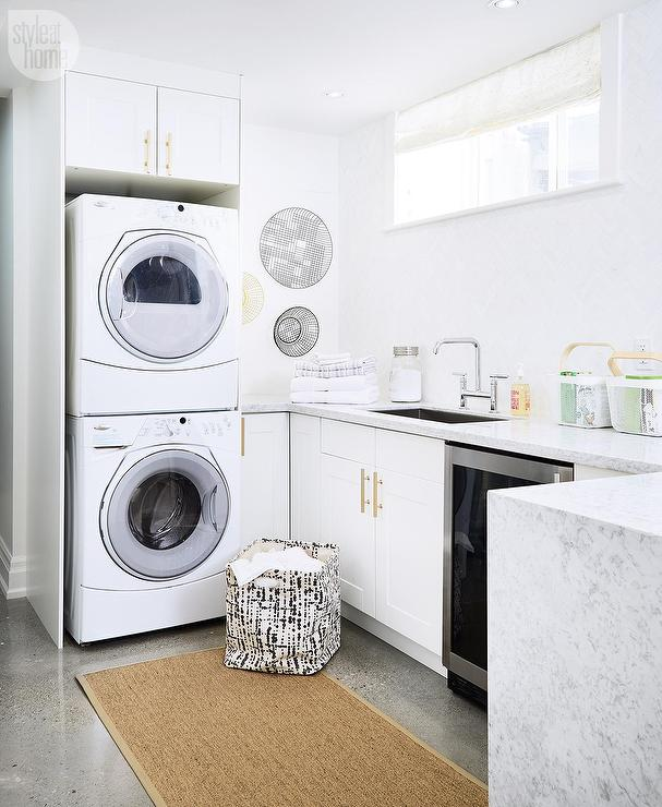... Laundry Basket Placed Beside An Enclosed Stacked Washer And Dryer  Positioned Beside White And Gray Waterfall Counters Sat Atop White Ikea  Cabinets ...