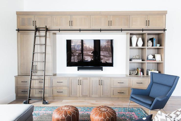 This Country Living Room Features A Flat Screen Television Surrounded By Beige Built In Cabinets Fitted With Pulls And Styled Bookcase
