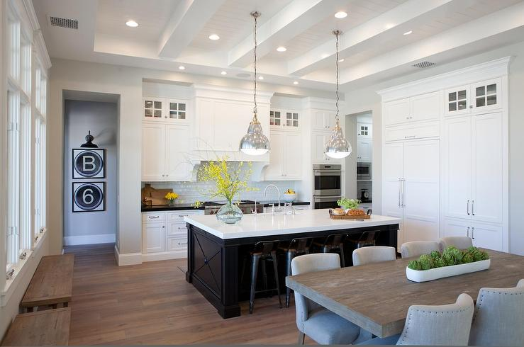 white kitchen with black center island and black industrial stools center island lighting