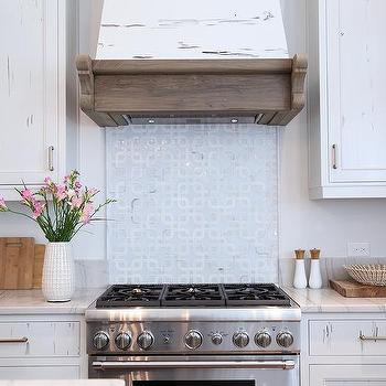 steel range sat against light blue geometric cooktop backsplash