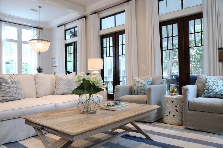 Charming Cottage Living Room Boasts A Wall Lined With Black Glass French Patio Doors And Transom Windows Dressed In Long White Linen Curtains Facing