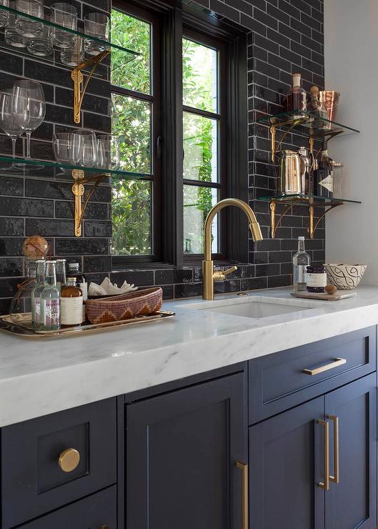 chic wet bar features dark blue shaker cabinets adorned with brushed