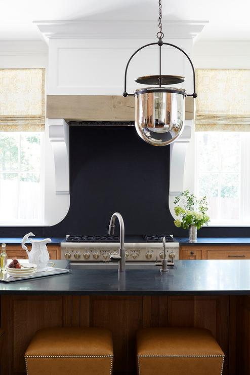 Maple kitchen cabinets with black countertops and backsplash