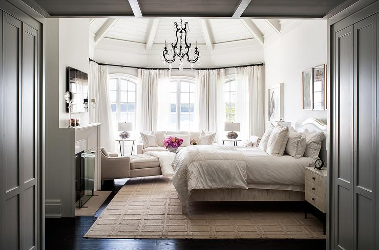 White And Gray Master Bedroom With Bed Facing Fireplace