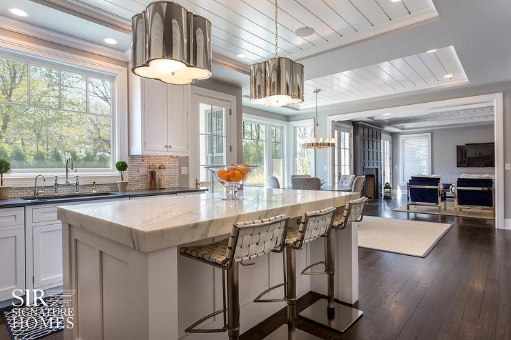 Kitchen island with white woven leather counter stools and Shiplap tray ceiling