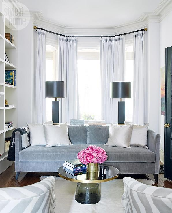 Living Room Bay Window with White Curtains with Gray Trim and Gray Velvet  Sofa