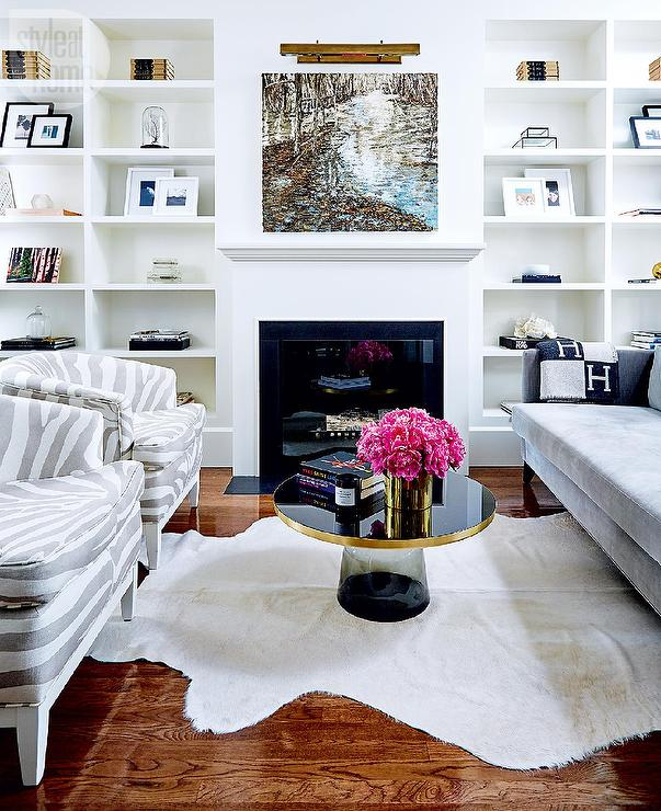 white and gray living room boasts built in shelves flanking a painting lit a bronze picture light mounted over a white fireplace mantel