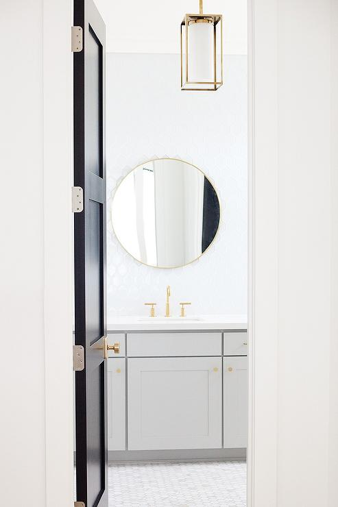 Gray And Gold Bathroom With Black Door And Brass Knob