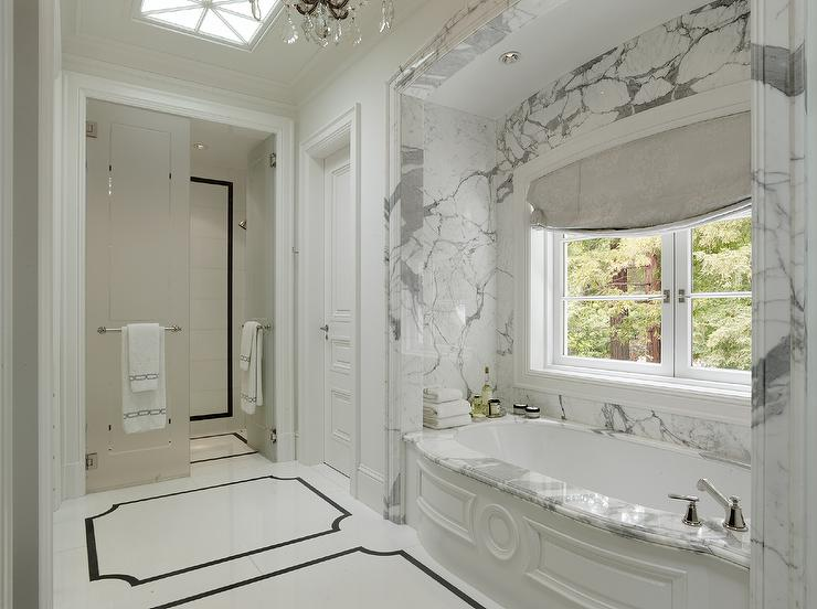 Marble Bathroom Nook With Wainscoted Bathtub And Skylight