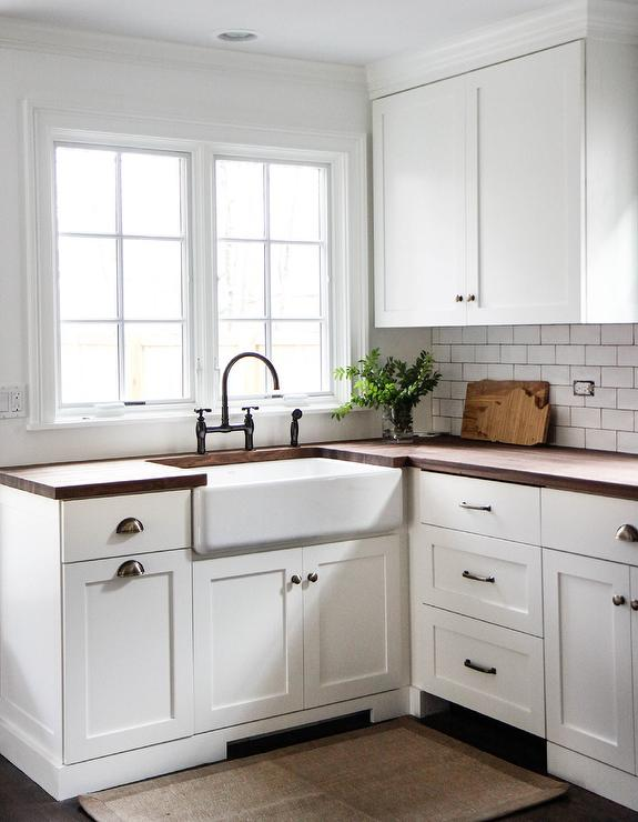 white shaker kitchen cabinets with wood countertops and farmhouse