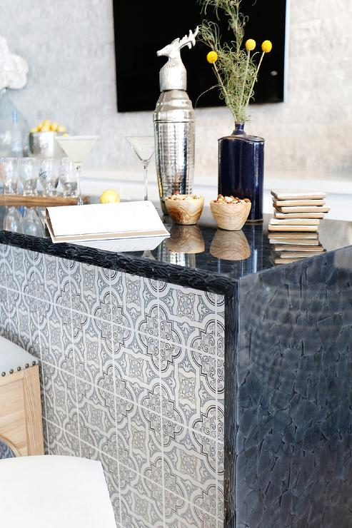 Blue Living Room Bar Features A Bar Island Covered In Blue Hand Stamped  Carrera Quatrefoil Tiles Topped With A Black Waterfall Countertop.