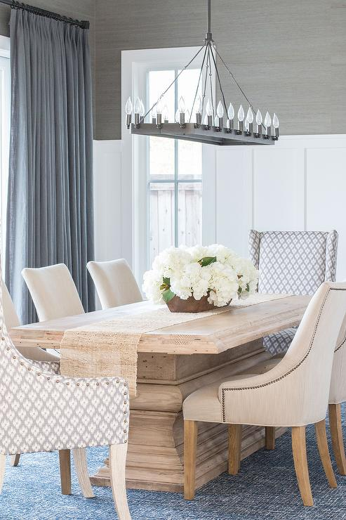 A Salvaged Wood Dining Table Accented With Burlap Runner Seats Six Cream Nailhead Chairs And Two Gray Ivory Head