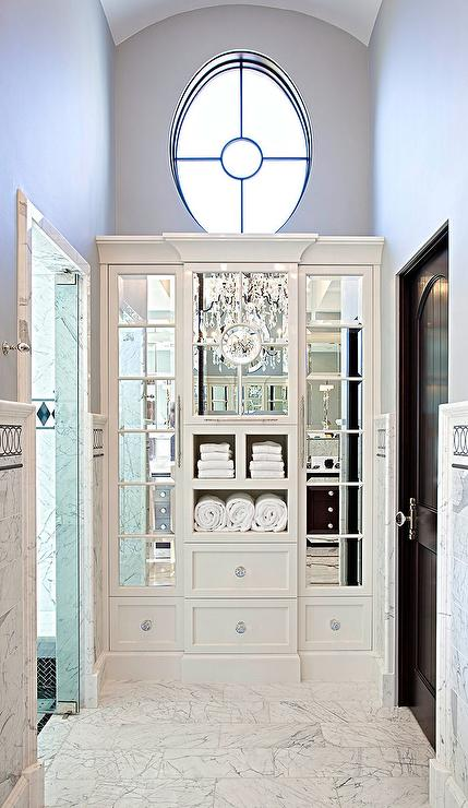 Chic Master Bathroom Boasts A Space Between A Walk In Shower And A Water  Closet Filled With White Built In Linen Cabinets Accented With Mirrored  Doors.