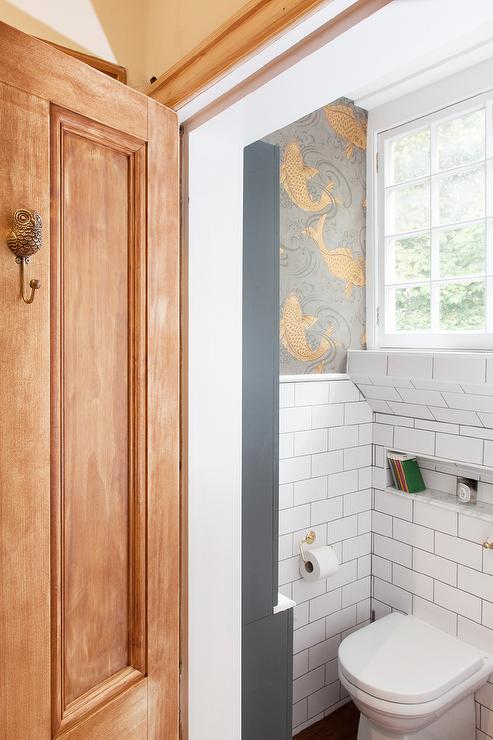 Chic water closet is filled with an upper wall clad in koi carp wallpaper, Osborne & Little Derwent Wallpaper, and a lower wall clad in white subway tiles ...