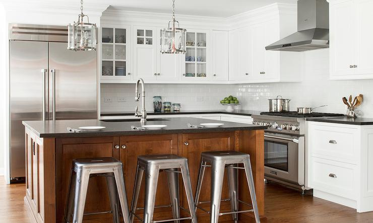 cherry stained kitchen island with black quartz countertops and tolix stools