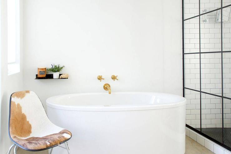 beautiful black and white bathroom boasts an oval tub by kohler accented with a wall mounted brass tub kohler purist bathtub faucet and a - Kohler Tub