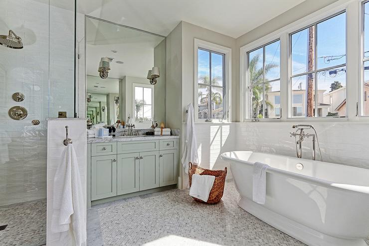 Natural Light Flows In Through Windows Lining A Bath Nook Fitted With A Freestanding Roll Top Tub Accented With A Polished Nickel Tub Filler Sat On Gray
