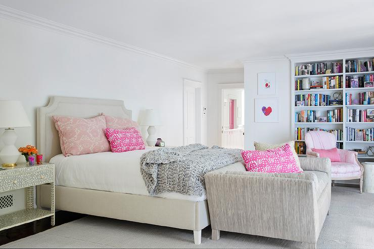 chic pink and gray bedroom boasts a light gray upholstered bed dressed in pink shams and a gray knitted throw blanket flanked by white and black bone inlay