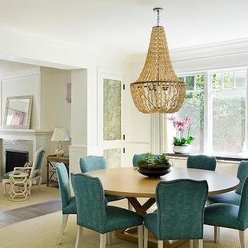 Round Blond Dining Table With Peacock Blue Chairs And Abalone Chandelier