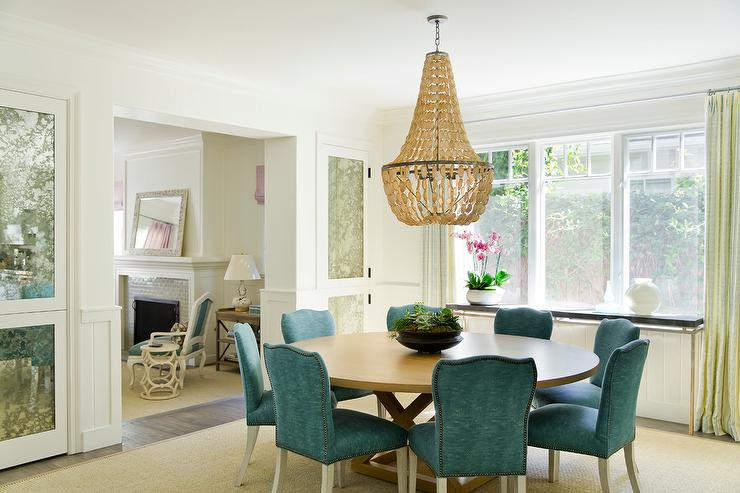 Round Blond Dining Table With Peacock Blue Dining Chairs And Abalone  Chandelier