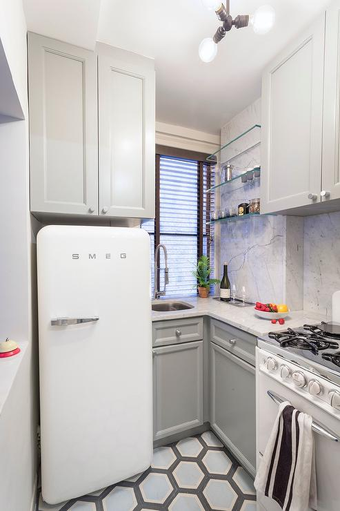 white fridge in kitchen. small gray kitchen with white smeg refrigerator fridge in w