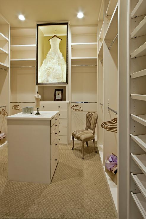 Large white walk in closet fitted with built in modular shelves boasts a custom lit