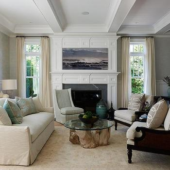 earth tone living room with cream camelback sofa and green and gray