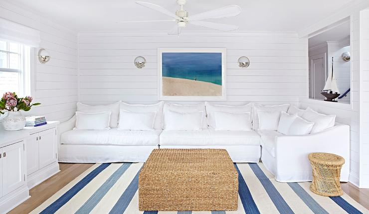 Welcoming White And Blue Beach Bungalow Living Room Features A Slipcovered Sectional Sat Under Framed Photo Flanked By Pelham Moon