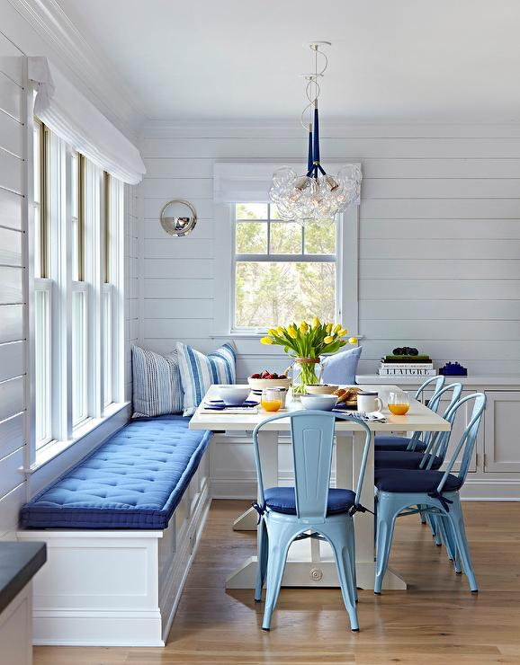 This Well Appointed Blue And White Beach Bungalow Dining Space Features A Built In L Shaped Banquette Sat Under Windows Dressed Roman